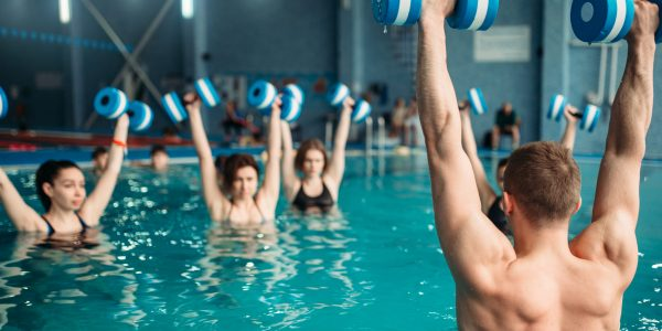 Female class with trainer on workout with aqua dumbbells in swimming pool. Women in swimwear on training, water sport
